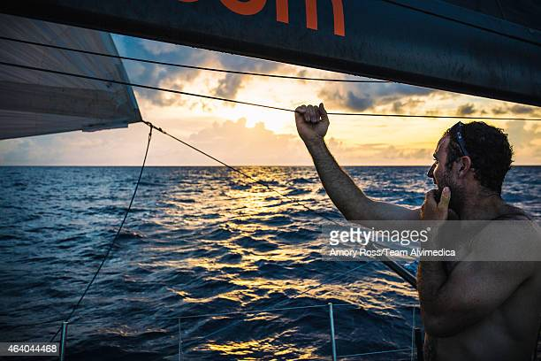 In this handout image provided by the Volvo Ocean Race onboard Team Alvimedica Seb Marsset looks to leeward where the sun just dipped below a rising...
