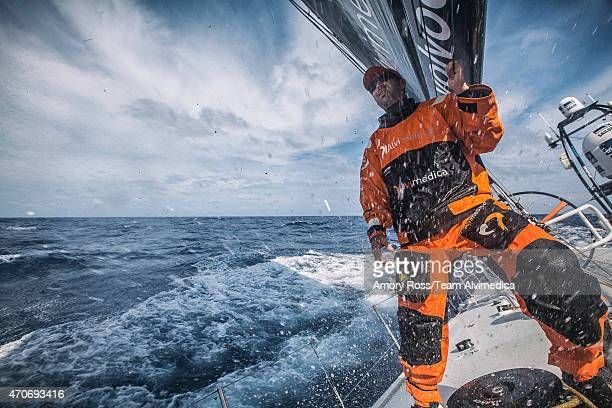 In this handout image provided by the Volvo Ocean Race onboard Team Alvimedica Seb Marsset peaks to leeward to critique the jib trim as spray shoots...