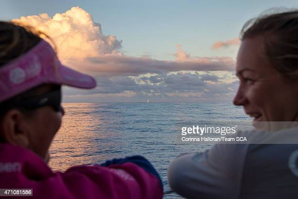 In this handout image provided by the Volvo Ocean Race onboard Team SCA Dee Caffari and Sophie Ciszek watch Team Brunel as the sun sets during Leg 6...