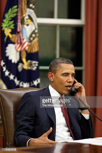 In this handout image provided by The White House President Barack Obama talks on the phone in the Oval Office before making a statement to the media...