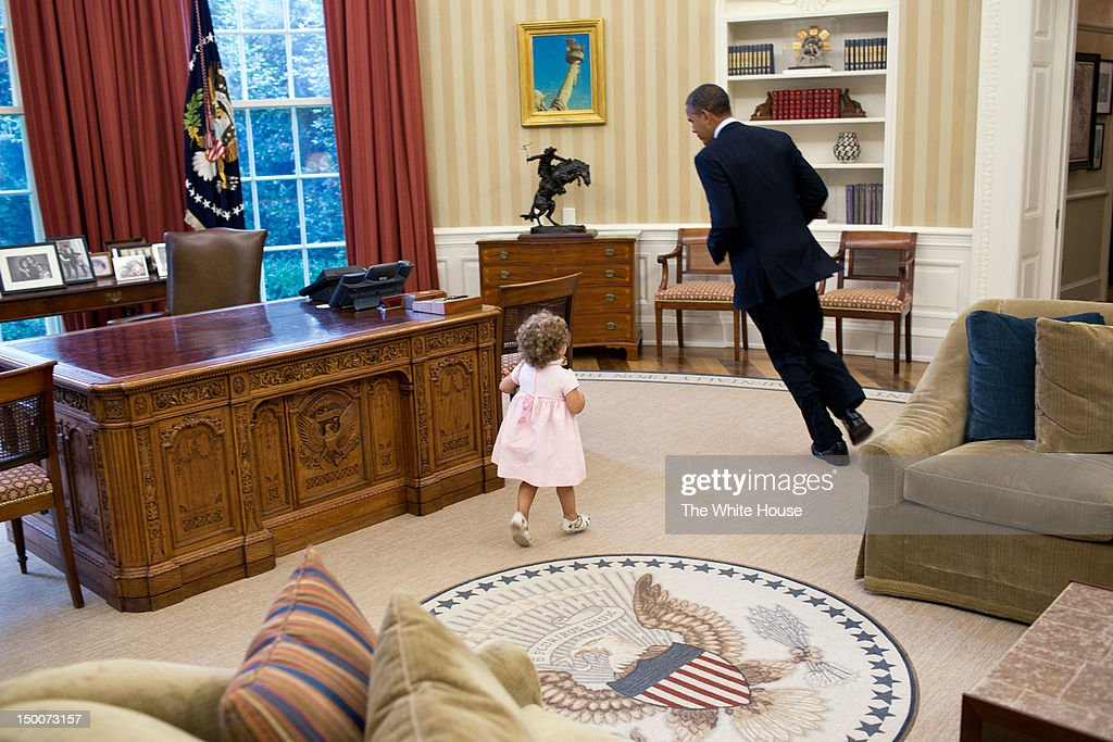 In this handout image provided by the White House, U.S. President Barack Obama plays with Sarah Froman, daughter of Nancy Goodman and Mike Froman, Deputy National Security Advisor for International Economics, in the Oval Office on July 9, 2012 in Washington, D.C.