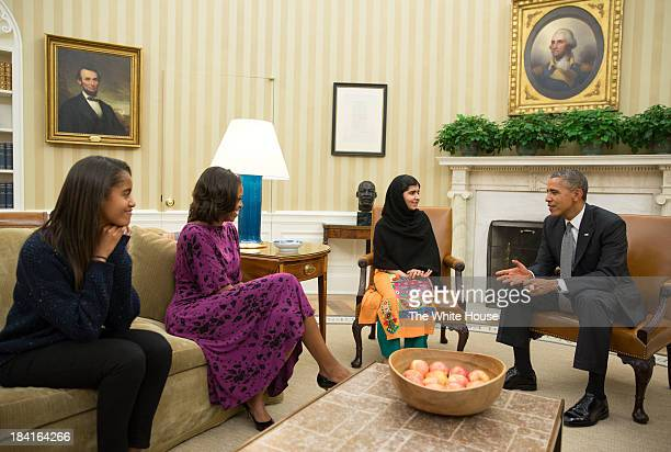 In this handout image provided by the White House US President Barack Obama first lady Michelle Obama and their daughter Malia Obama meet with Malala...