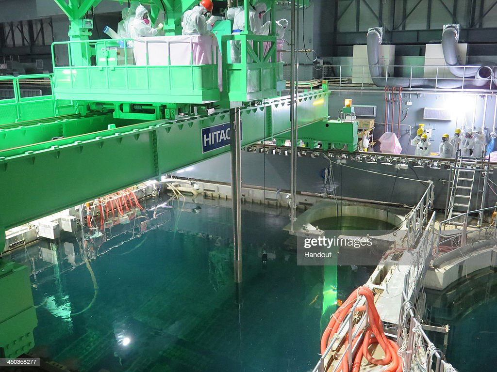 In this handout image provided by Tokyo Electric Power Co workers remove nuclear fuel rods from a pool at No 4 reactor of the Fukushima Daiichi...