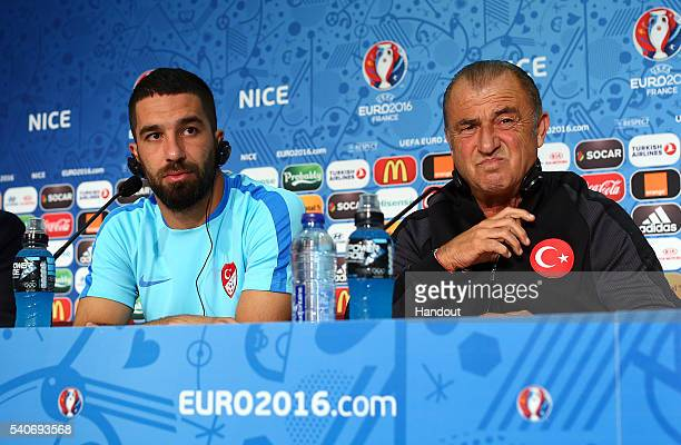 In this handout image provided by UEFA Arda Turan and coach Fatih Terim face the media during the Turkey Press Conference at Allianz Riviera Stadium...