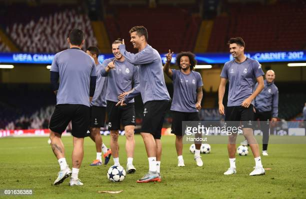 In this handout image provided by UEFA Cristiano Ronaldo of Real Madrid shares a joke with team mates Gareth Bale and Marcelo during a training...