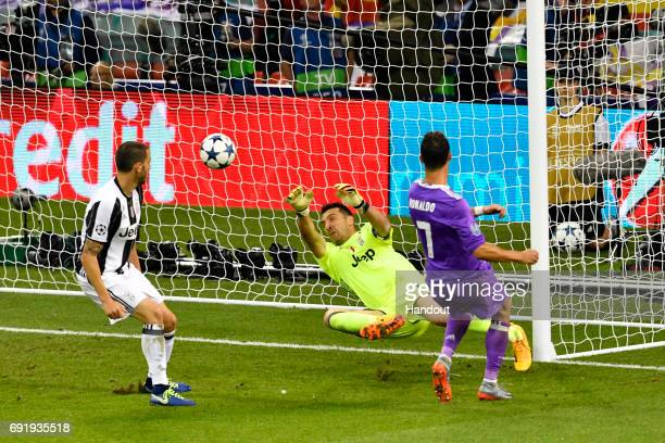 In this handout image provided by UEFA Cristiano Ronaldo of Real Madrid scores his sides third goal during the UEFA Champions League Final between...