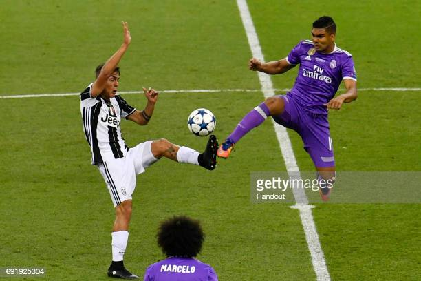 In this handout image provided by UEFA Paulo Dybala of Juventus and Casemiro of Real Madrid battle for possession during the UEFA Champions League...