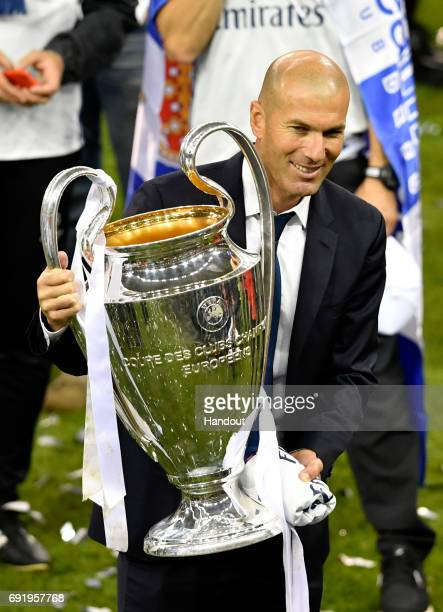In this handout image provided by UEFA Zinedine Zidane coach of Real Madrid carries the trophy after the UEFA Champions League Final between Juventus...