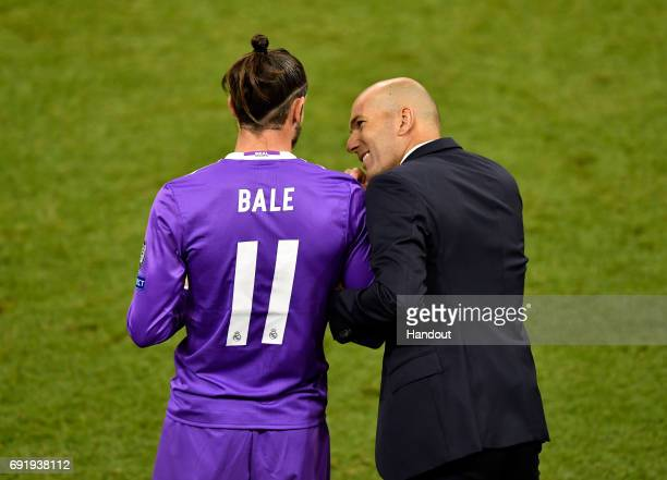 In this handout image provided by UEFA Zinedine Zidane Manager of Real Madrid speaks to Gareth Bale of Real Madrid before he is subbed on during the...