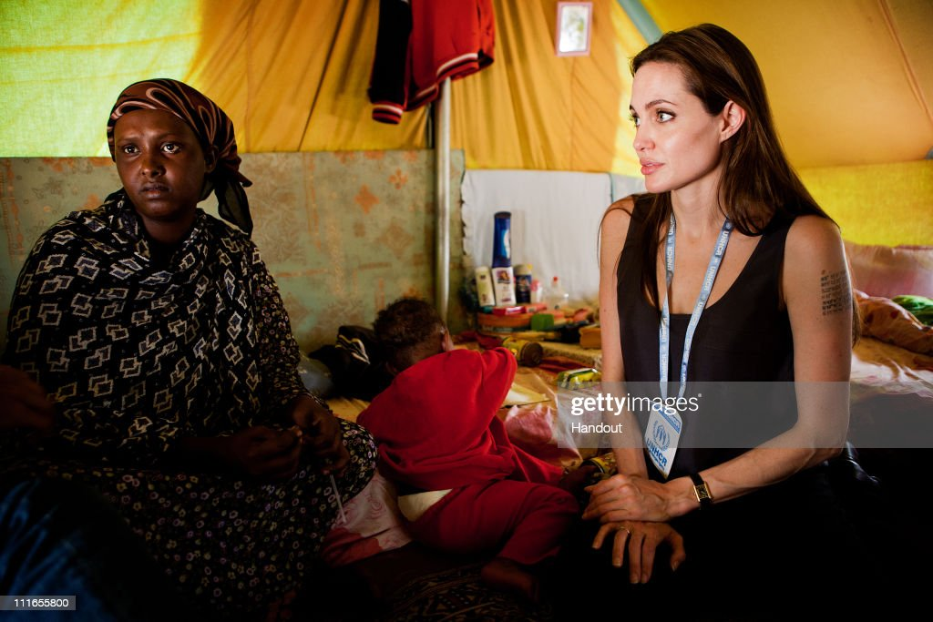 In this handout image provided by UNHCR, UNHCR Goodwill Ambassador <a gi-track='captionPersonalityLinkClicked' href=/galleries/search?phrase=Angelina+Jolie&family=editorial&specificpeople=201591 ng-click='$event.stopPropagation()'>Angelina Jolie</a> visits Somali refugees at Shousha Camp located eight kilometres from the Tunis-Libyan border on April 5, 2011 at Ras Djir, Tunisia. The actress travelled to the camp in Tunisia to encourage continued funding and support from the international community to further assist the hundreds of thousands of people who have crossed into Tunisia to escape the violence in Libya.