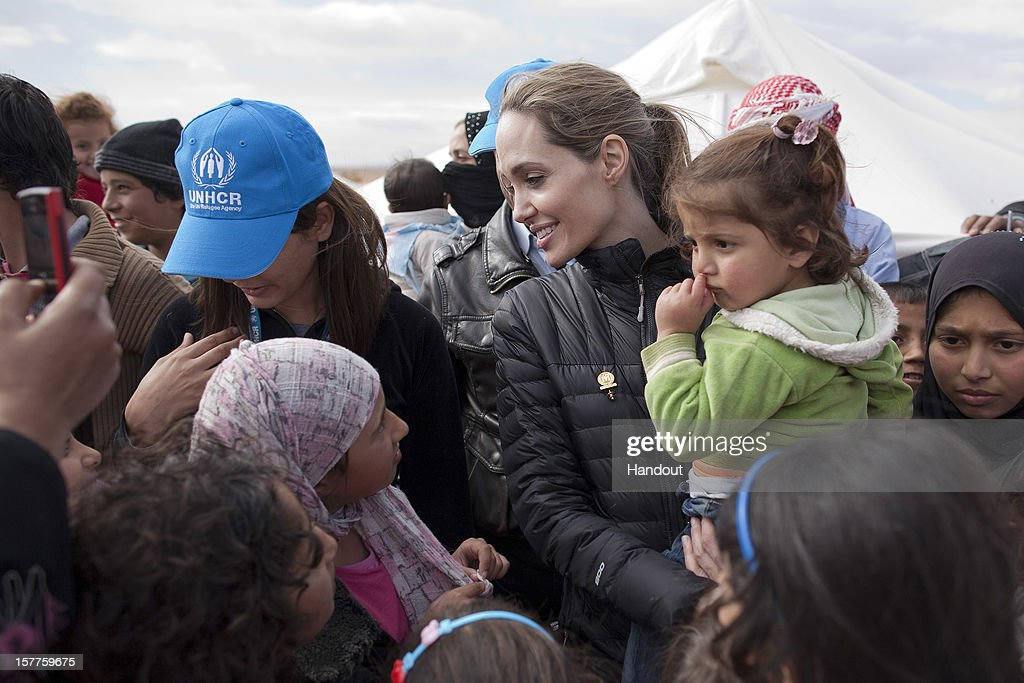 In this handout image provided by UNHCR, UNHCR Special Envoy <a gi-track='captionPersonalityLinkClicked' href=/galleries/search?phrase=Angelina+Jolie&family=editorial&specificpeople=201591 ng-click='$event.stopPropagation()'>Angelina Jolie</a> meets with refugees at the Zaatari refugee camp on December 6, 2012 outside of Mafraq, Jordan. Jolie said on her second visit to the region in three months civilians inside the country are being targeted. Many of those trying to flee are exposed to extreme danger right up to the border itself. Since her last visit to the region in September, the number of refugees in the region has increased by more than 200,000 and in Jordan alone by nearly 50,000.