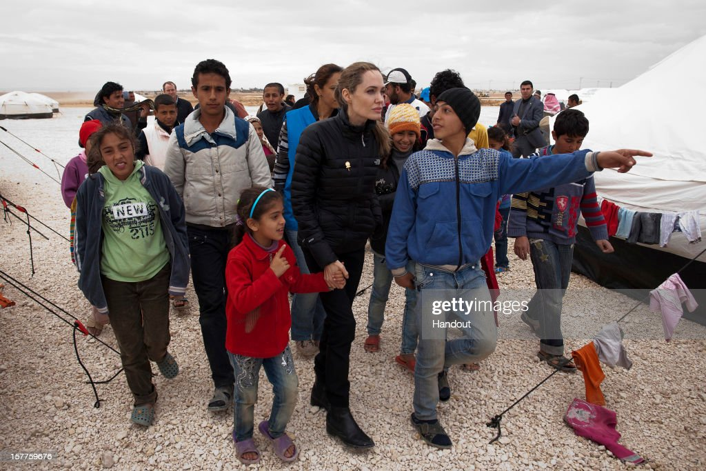 In this handout image provided by UNHCR UNHCR Special Envoy Angelina Jolie meets with refugees at the Zaatari refugee camp on December 6 2012 outside...