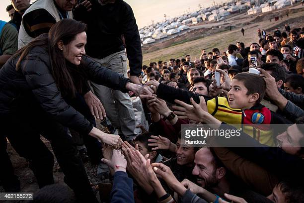 In this handout image provided by UNHCR UNHCR Special Envoy Angelina Jolie meets members of the Yazidi minority in Khanke IDP Camp on January 25 2015...