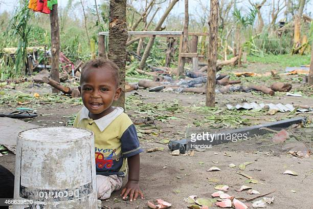 In this handout image provided by UNICEF a young boy from the Taunono community looks on after the community was completely destroyed by Cyclone Pam...