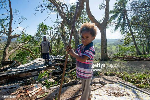In this handout image provided by UNICEF three year old Rachel helps her father Ken as they clear away the debris when their house was washed away...