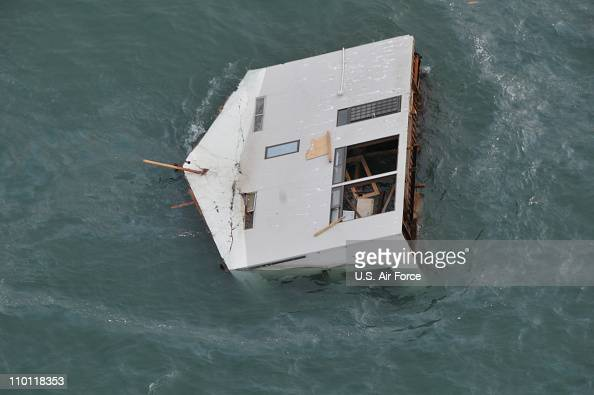In this handout image provided by US Air Force a house is seen adrift off the coast of northeastern Japan from a HH60G helicopter surveying the...