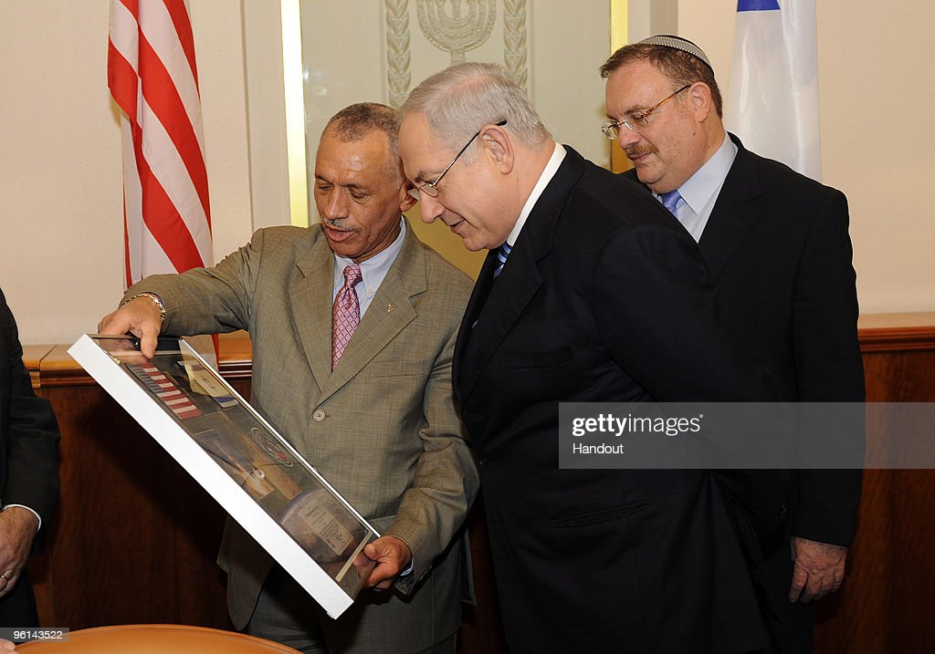 In this handout image provided by U.S. Embassy Tel-Aviv, NASA Administrator Charles F. Bolden, Jr. (L) presents a photo montage to Israeli Prime Minister Benjamin Netanyahu (C) with flags of the USA and Israel and mission patch January 24, 2010 in Jerusalem, Israel. These flags of the United States and Israel were flown aboard the Space Shuttle Atlantis during the STS-129 assembly mission to the international space station. November 16-27, 2009. The mission patch was flown on STS-J1, space shuttle Discovery, piloted by Charles F. Bolden, Jr. April 24 - 29, 1990. They met to discuss past and future bilateral cooperation in space science research and exploration.
