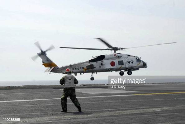 In this handout image provided by US Navy an SH70B helicopter from the Japan Maritime SelfDefense Force lands aboard the aircraft carrier USS Ronald...