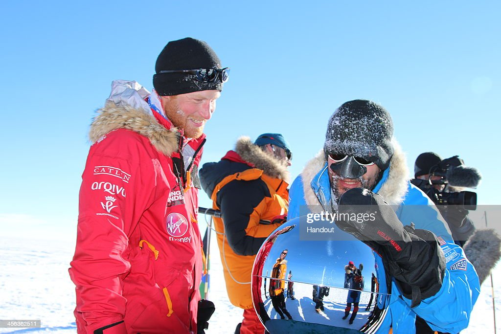 In this handout image provided by Walking with the Wounded, Prince Harry (L) and Ivan Castro touch the pole as they and their fellow adventurers reach the South Pole as part of their Walking With The Wounded charity trek on December 13, 2013 in Antartica. The Virgin Money South Pole Allied Challenge 2013, of which Prince Harry is patron, will see the participants race across three degrees to the South Pole. All 12 injured service personnel from Britain, America, Canada and Australia have overcome life-changing injuries and undertaken challenging training programmes to prepare themselves for the conditions they will face in Antarctica. Trekking around 15km to 20km per day, the teams endured temperatures as low as minus 45C and 50mph winds as they pulled their 70kg sleds to the south pole.