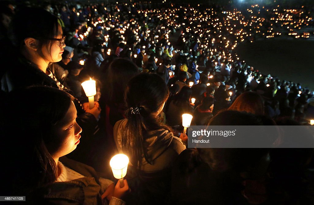 In this handout image provided by Won Dae-Yeon-Donga Daily, Danwon high school students and citizens hold candles as they pray for the safe return of passengers of a sunken ferry on April 20, 2014 in Ansan, South Korea. At least 58 people are reported to have died and 244 are still missing. The ferry identified as the Sewol was carrying about 470 passengers, including students and teachers, and was travelling to Jeju Island.