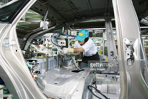 In this handout image released by Toyota Motor Corporation a Toyota employee uses a special loading device to install the Prius' hybridsystem battery...
