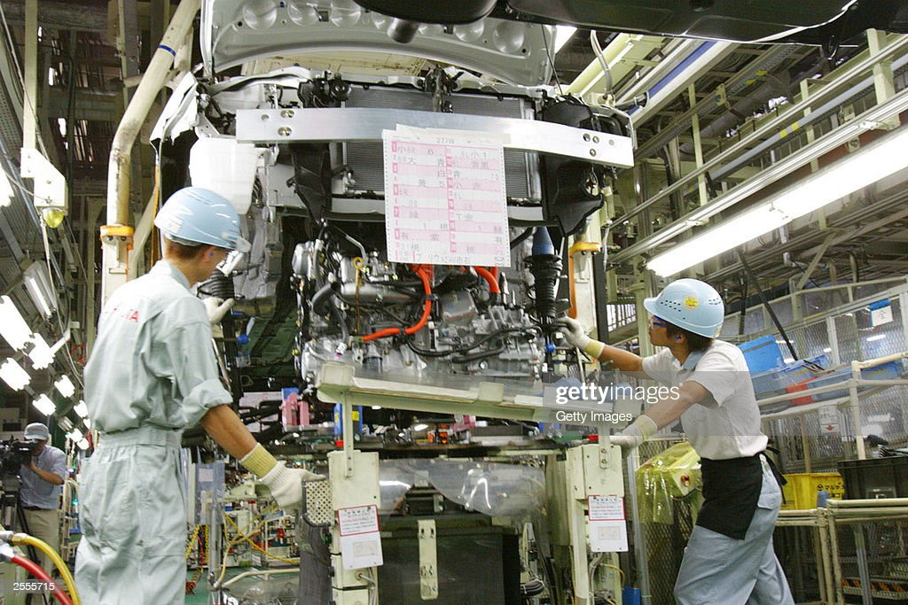 In this handout image released by Toyota Motor Corporation Toyota employees install a hybrid motor engine unit from below the body of a Prius at...