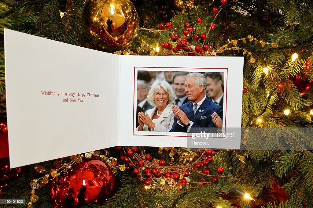 THE PRINCE OF WALES WOULD BE GRATEFUL IF PUBLICATIONS WHO USE THE CARD/PHOTOGRAPH CONSIDER MAKING A DONATION TO 'AID TO THE CHURCH IN NEED.') In this handout image released on December 13, 2014 by Clarence House, shows the personal Christmas card produced for <a gi-track='captionPersonalityLinkClicked' href=/galleries/search?phrase=Camilla+-+Hertiginna+av+Cornwall&family=editorial&specificpeople=158157 ng-click='$event.stopPropagation()'>Camilla</a>, Duchess of Cornwall and Prince Charles, Prince of Wales, featuring them in a photograph by Christopher Jackson of Getty Images with the couple laughing during the Invictus Games Opening Ceremony on September 10, 2014 hangs on a Christmas tree on December 11, 2014 in London, England.