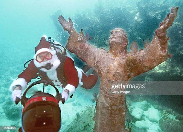 In this handout image Spencer Slate dressed as Santa Claus is towed by an underwater scooter around the Christ of the Deep statue December 23 2003 in...
