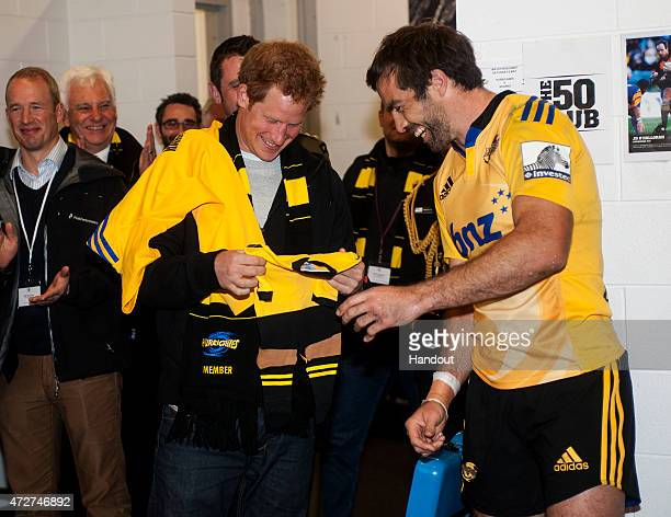 In this handout image supplied by Dave Lintott Hurricanes captain Conrad Smith presents Prince Harry with a personalized onesie for his niece...