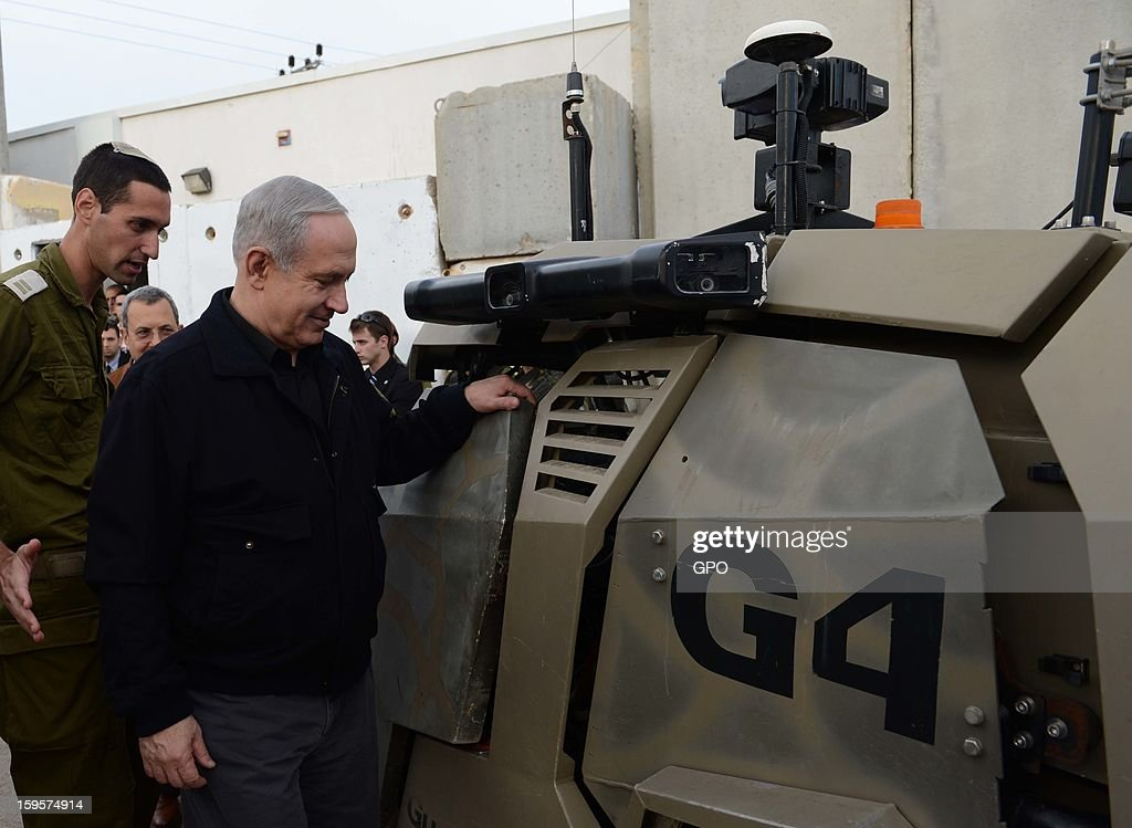 In this handout image supplied by GPO, Israeli Prime Minister Benjamin Netanyahu and Minister of Defense Ehud Barak visit a base at the Gaza border on January 16, 2013 at an unpecified location, Israel.