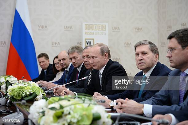 In this handout image supplied by Host Photo Agency / RIA Novosti President of the Russian Federation Vladimir Putin attends a meeting with President...