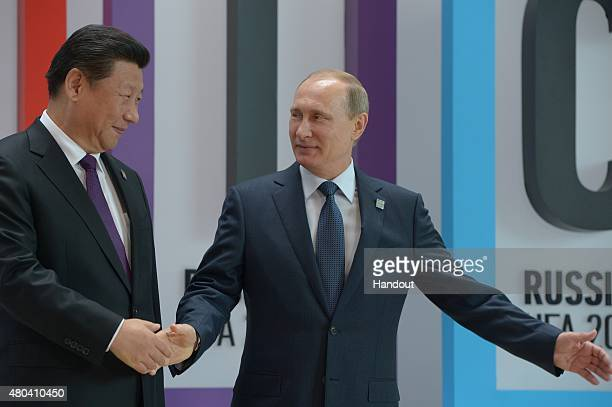 In this handout image supplied by Host Photo Agency / RIA Novosti President of the Russian Federation Vladimir Putin right and President of the...