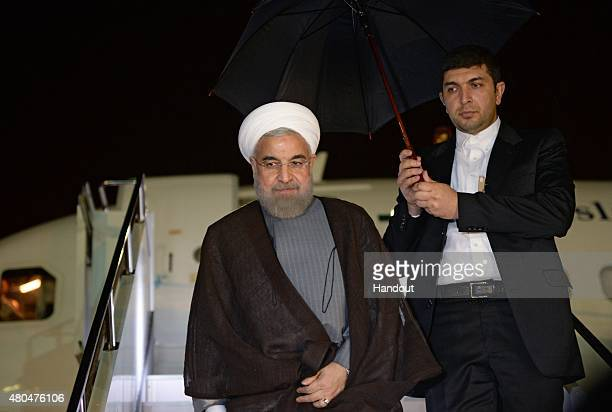 In this handout image supplied by Host Photo Agency / RIA Novosti President of the Islamic Republic of Iran Hassan Rouhani arrives at the Ufa airport...