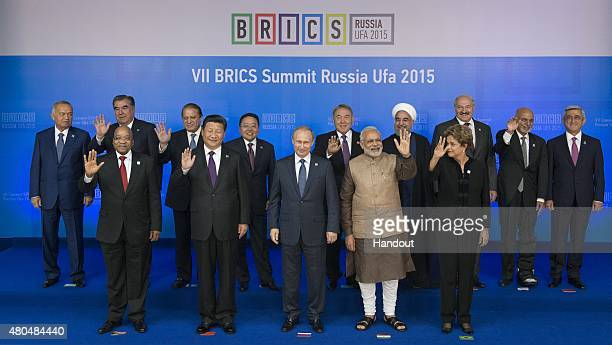 In this handout image supplied by Host Photo Agency / RIA Novosti President of the Russian Federation Vladimir Putin centre during a group photograph...