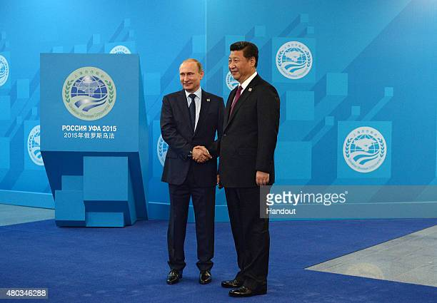 In this handout image supplied by Host Photo Agency / RIA Novosti Russian President Vladimir Putin and President of China Xi Jinping shake hands...