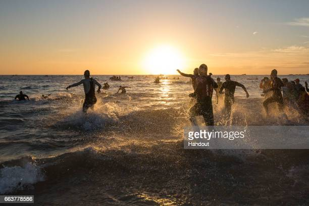 In this handout image supplied by Ironman Athletes enter the water during the 38km Swim while competing in the Ironman South Africa race at Port...