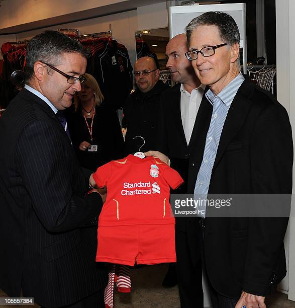 In this handout image supplied by Liverpool Football Club John W Henry of NESV with a baby football kit in the Liverpool FC shop at Anfield on...
