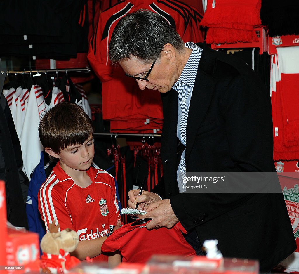 In this handout image supplied by Liverpool Football Club, John W Henry of NESV signs an autograph for a young fan in the Liverpool F.C. shop at Anfield on October 16, 2010 in Liverpool, England. Henry's New England Sports Ventures (NESV) successfully completed the £300million takeover of Liverpool following a bitter legal battle with former owners Tom Hicks and George Gillett.