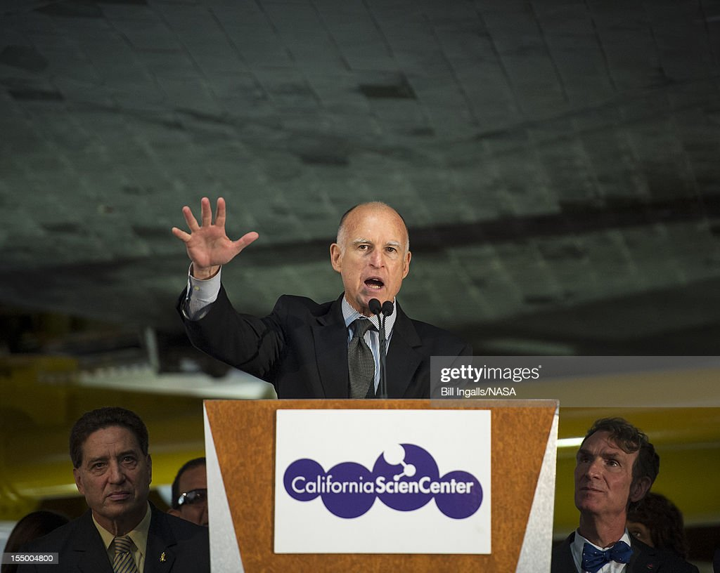 In this handout image supplied by NASA, California Governor Jerry Brown speaks from a podium underneath the space shuttle Endeavour during the grand opening ceremony for the California Science center's Samuel Oschin Space Shuttle Endeavour Display Pavilion, on October 30, 2012, in Los Angeles, California. Endeavour, built as a replacement for space shuttle Challenger, completed 25 missions, spent 299 days in orbit, and orbited Earth 4,671 times while traveling 122,883,151 miles.
