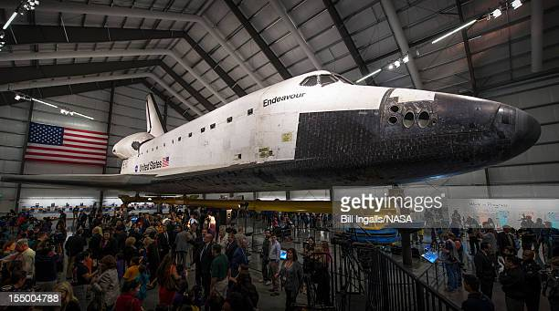 In this handout image supplied by NASA Guests walk around space shuttle Endeavour after the grand opening ceremony for the California Science...