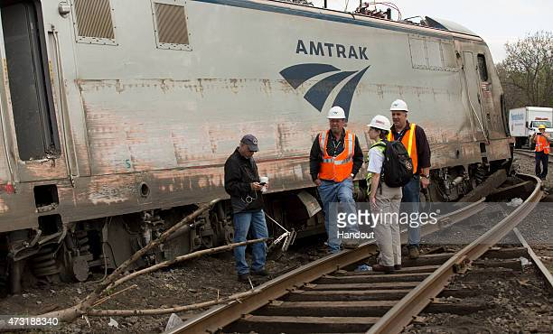 In this handout image supplied by NTSB NTSB Recorder Specialist Cassandra Johnson works with officials on the scene of the Amtrak Train derailment on...