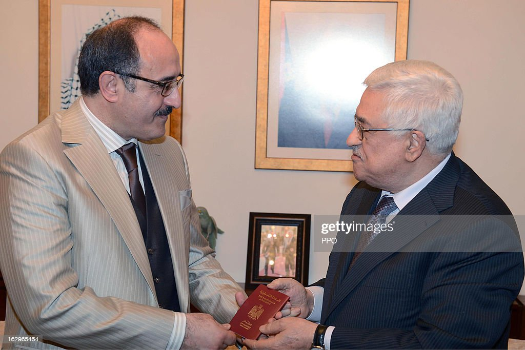 In this handout image supplied by PPO, Palestinian President Mahmoud Abbas (R) gives Tunisian/Lebanese journalist Ghassan bin Jiddo Palestinian citizenship March 2, 2013 in Oman.