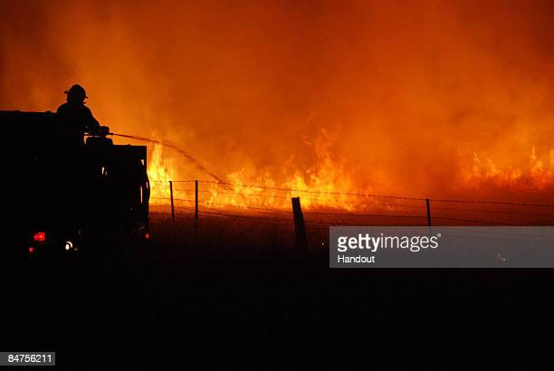 In this handout image supplied by Stephen Henderson of the County Fire Authority A firefighter of the CFA Strike Teams fights the blaze during the...