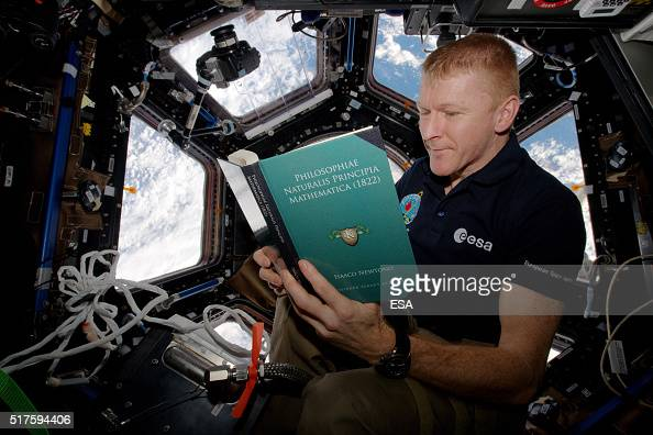 In this handout image supplied by the European Space Agency ESA astronaut Tim Peake reads a copy of Principia on World Book Day on the International...