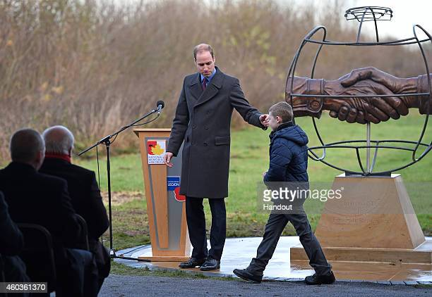 In this handout image supplied by The FA Prince William Duke of Cambridge and tenyearold Spencer Turner who designed the memorial help unveil the...