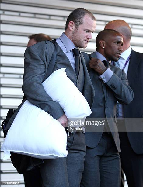 In this handout image supplied by the FA Wayne Rooney of England carries a pillow as he and team mate Jermain Defoe prepare to board a plane leaving...