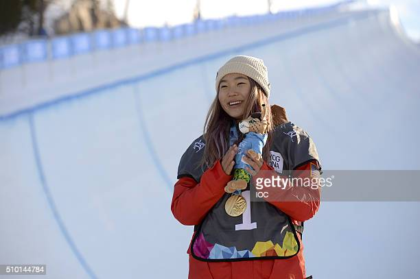 In this handout image supplied by the IOC Chloe Kim of the United States poses on the medal podium after winning the Ladies' Snowboard Halfpipe...