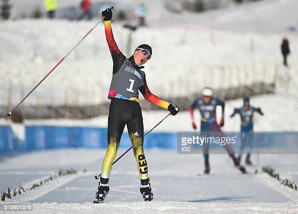 In this handout image supplied by the IOC Tim Kopp of Germany crosses the line to win the Nordic Combined Men's Individual Gundersen NH/5km...