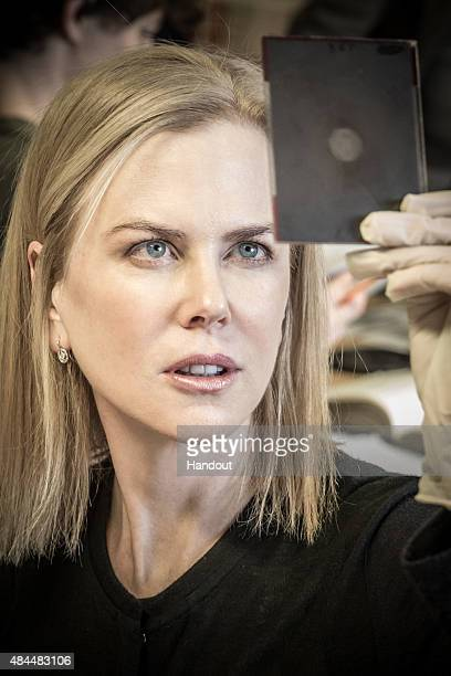In this handout image supplied by The Michael Grandage Company actress Nicole Kidman views the original slide of Photograph 51 taken by Rosalind...