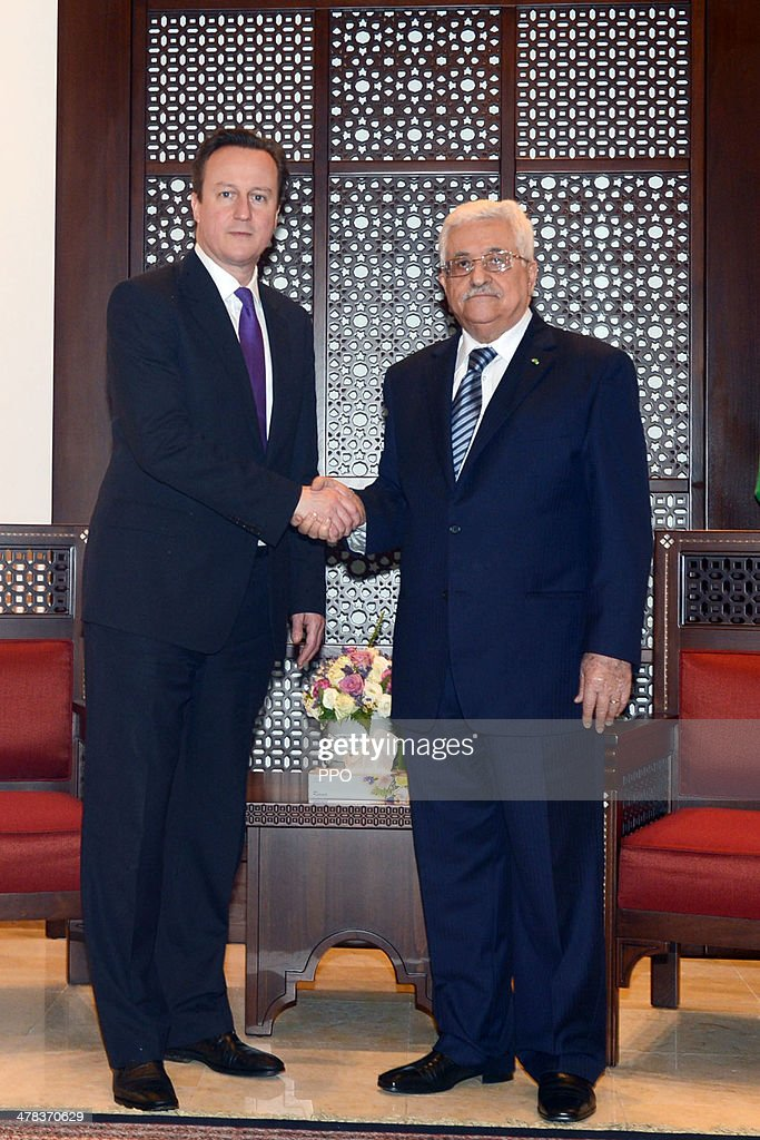 In this handout image supplied by the Palestinian Press Ofiice Palestinian Authority President Mahmoud Abbas shakes hands with British Prime Minister...
